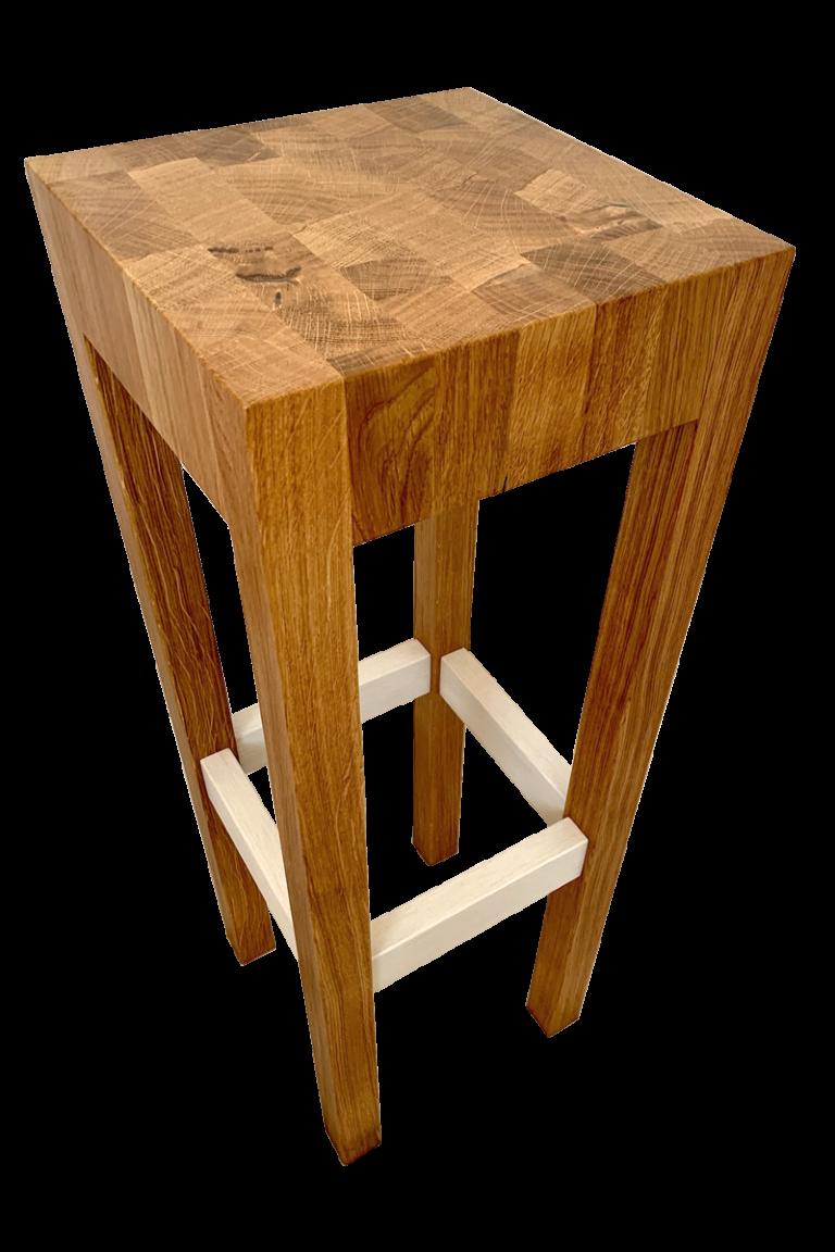 Masivní, řemeslně zpracovaná a přesto subtilně působící židle s výrazným sedákem a kresbou letokruhů, trnož mořená bíle. Výšku lze upravit na přání, stejně jako barvu trnože.